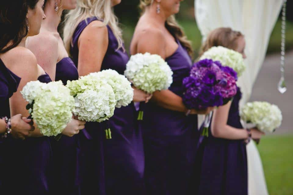 Bridemaids lined up at alter wearing Purple dresses holding white spring flower bouquets