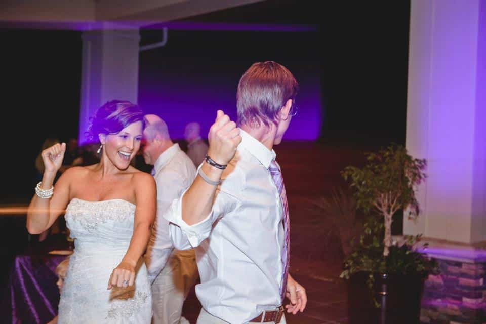 Bride dancing with family with purple uplight in the background done by Our Dj Rocks