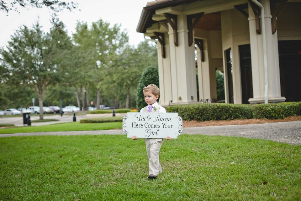 ring bearer walking down asile holding a sign stating here comes your bride