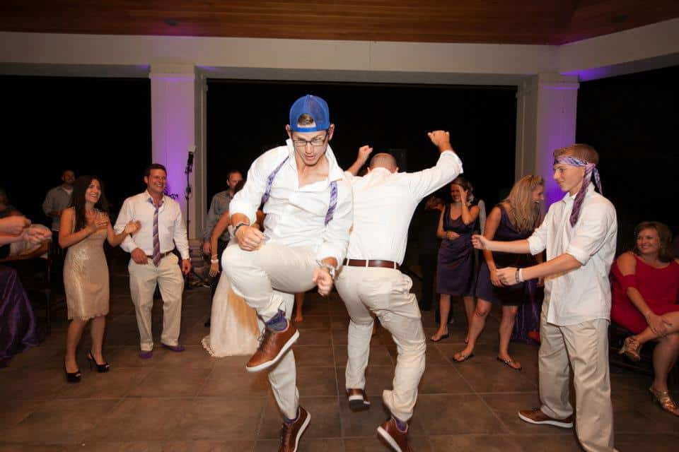 Circle surrounding dance floor with groomsmen dancing and showing off best moves