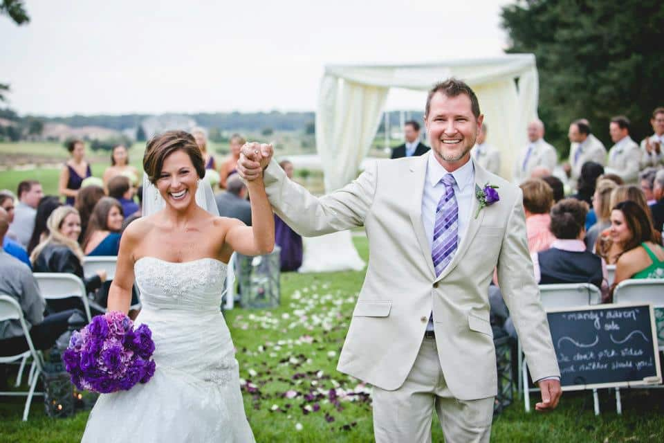 Bride and groom walking back down as a married couple. Hands in air and smiles