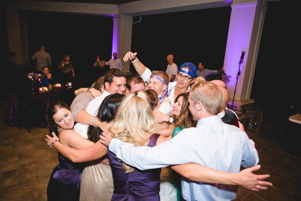 group hug with bride and groom in middle