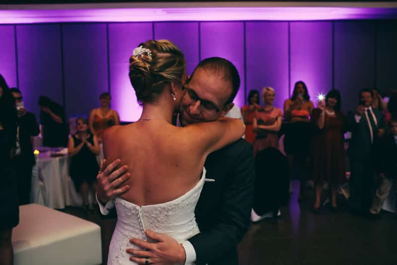 Bride and Groom sharing their first dance at Winter Park civic center with pruple uplighiting done by Our DJ Rocks