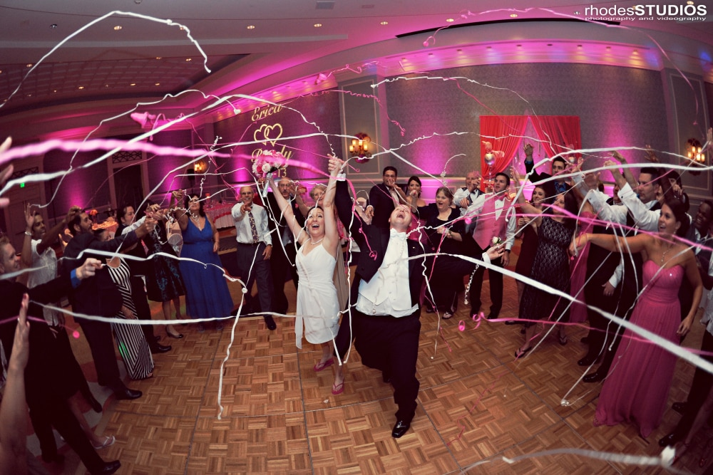 "One final ""hooray!"" With everyone on the dance floor with bride nd groom and ribbon wands waving in the air; hot pink uplighting and cusomized monogram at Onmi Champions Gate wedding done by Our DJ Rocks"