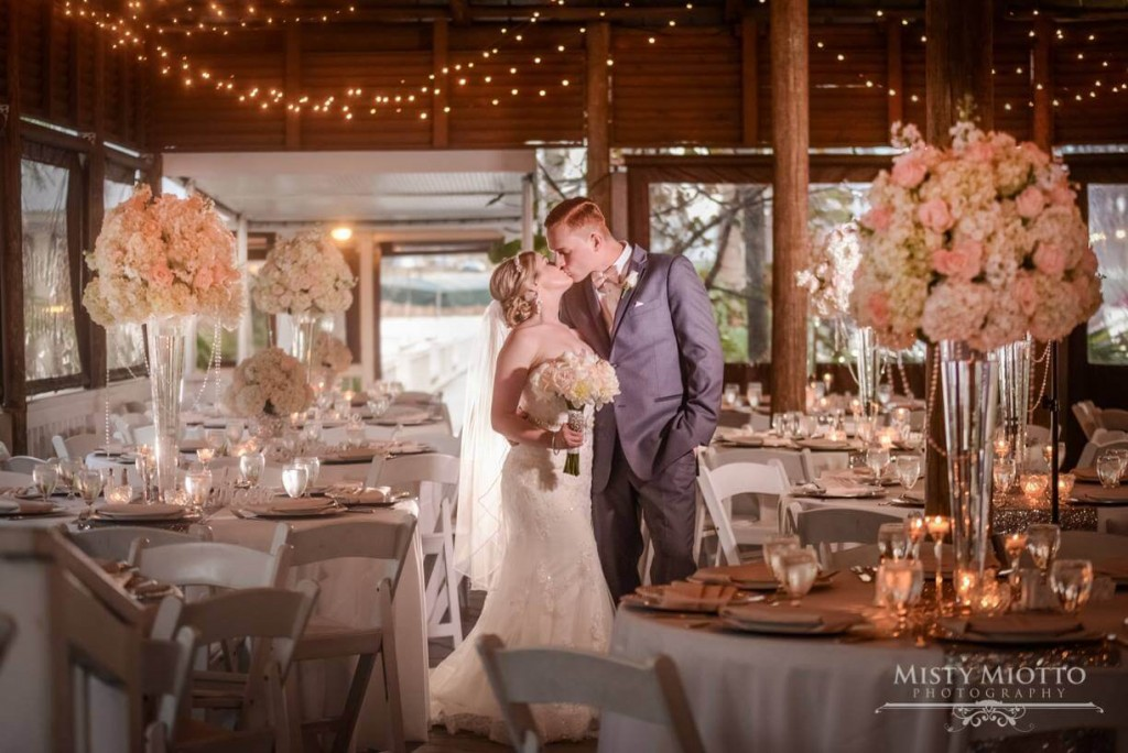Bride and groom wedding photo. Tall flower centerpieces.