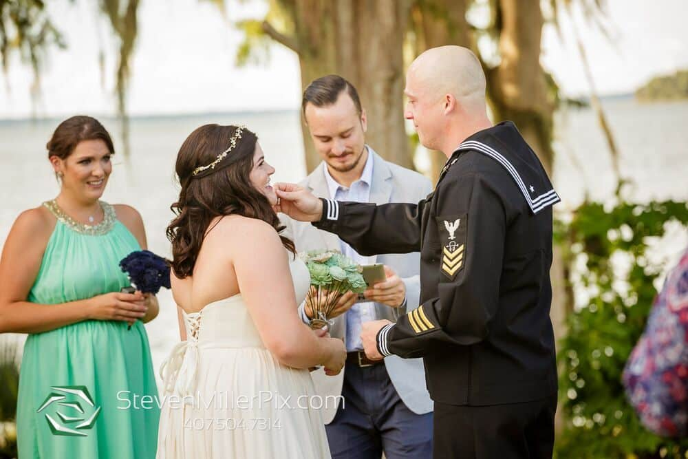 steven miller photography Bride and groom at alter. Corset wedding dress. Green bridesmaid dress. Wedding hair piece.