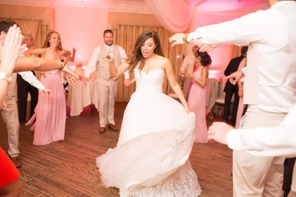 Bride dancing on wooden dance floor. Lace wedding dress. Light pink uplighting.