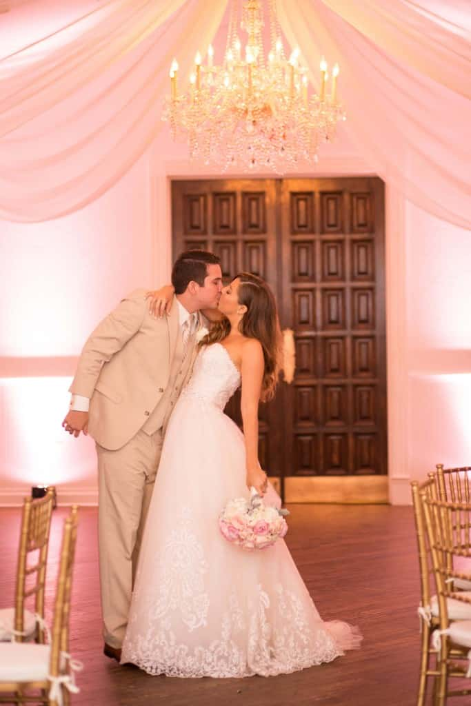 Bride and groom kissing. Cute wedding photo. Lace wedding dress. Tan tuxedo. Light pink uplighting.