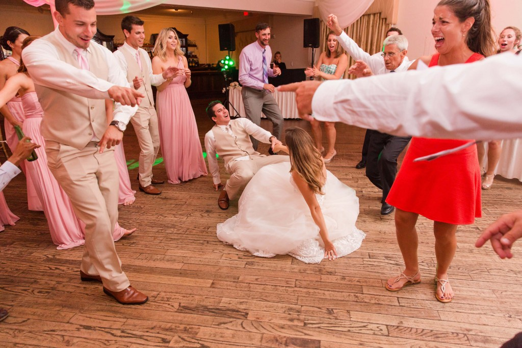 Bride and groom dancing at wedding. Break dancing at wedding. Tan tuxedo.