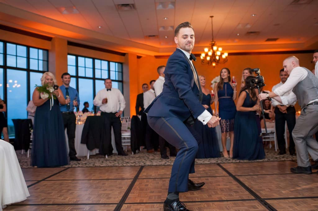 Wedding at Bella Collina. Groom dancing. Groom twerking. Amber uplighting. Navy tux. Navy bridesmaid dresses.