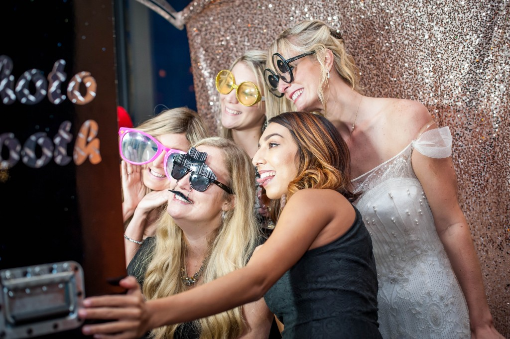 Photo booth at wedding. Wedding dress with side sleeves. Giant glasses. Silly glasses. Gold sparkly backdrop.