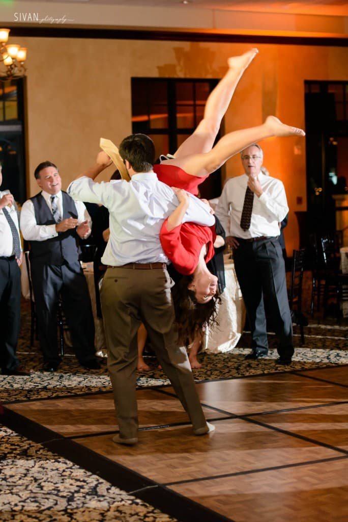 Swing dancing at wedding at Bella Collina on wooden dance floor with amber uplighting