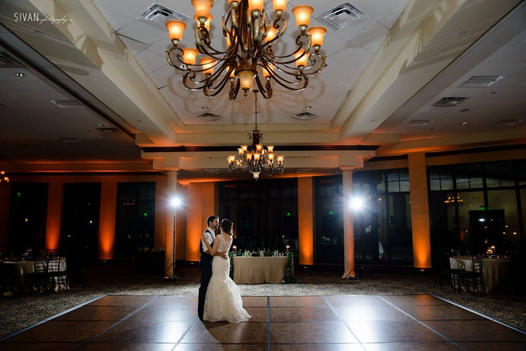 Bride and groom last dance at bella collina on wooden dance floor with amber uplighting and chandelier
