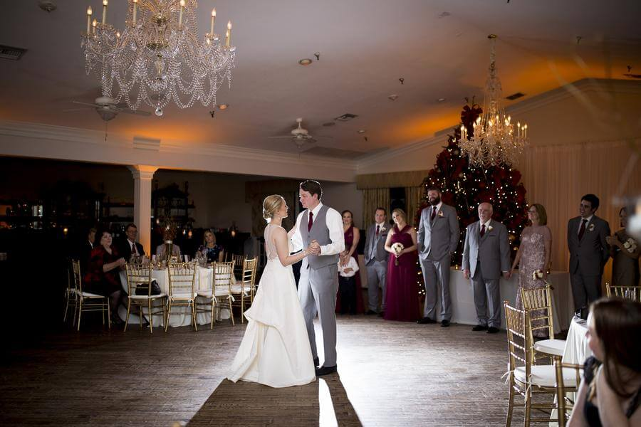 Bride and groom first dance at Highland Manor on wooden dance floor with amber uplights