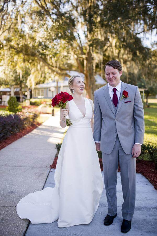 Bride and groom at Highland Manor. Red flower wedding bouquet. Grey wedding tuxedo. Simple white wedding dress.
