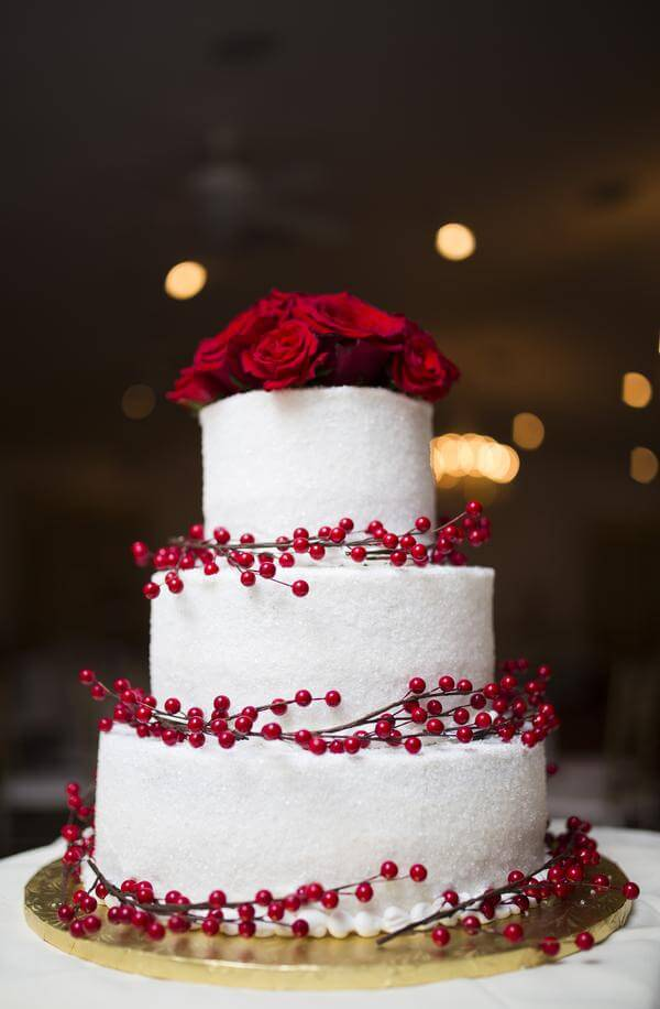 Wedding cake with white frosting and red roses and red berries