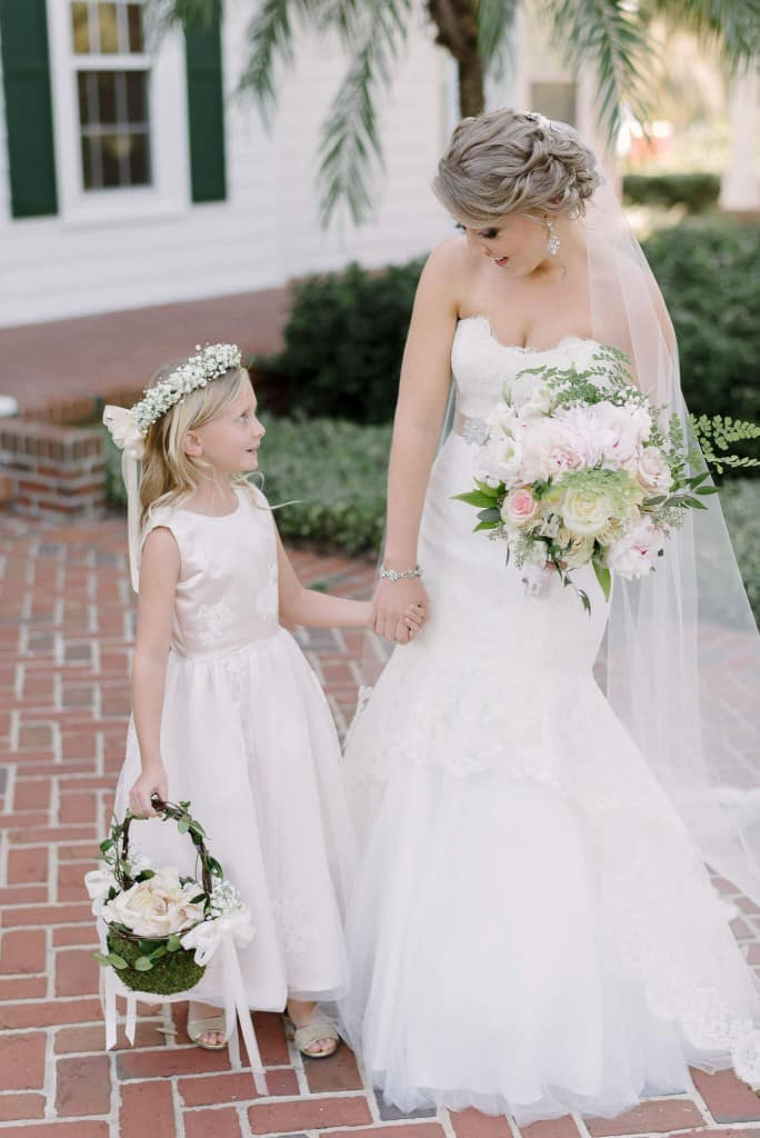 Cypress Grove wedding bride holding flower girl's hand with lace trumpet style wedding dress and light pink and green bouquet