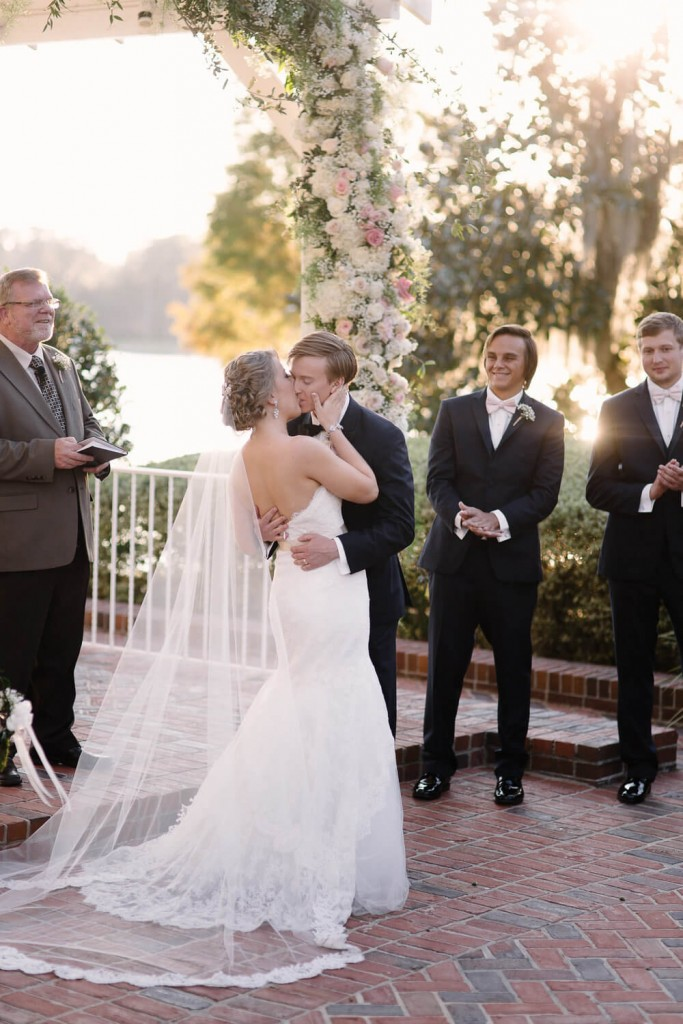 Cypress grove wedding ceremony under floral gazebo bride and groom kiss