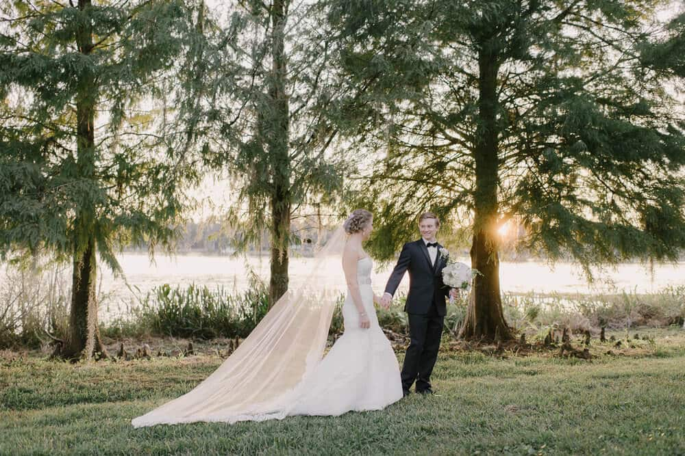cypress grove wedding photo of bride and groom in white trumpet lace wedding dress and black tuxedo