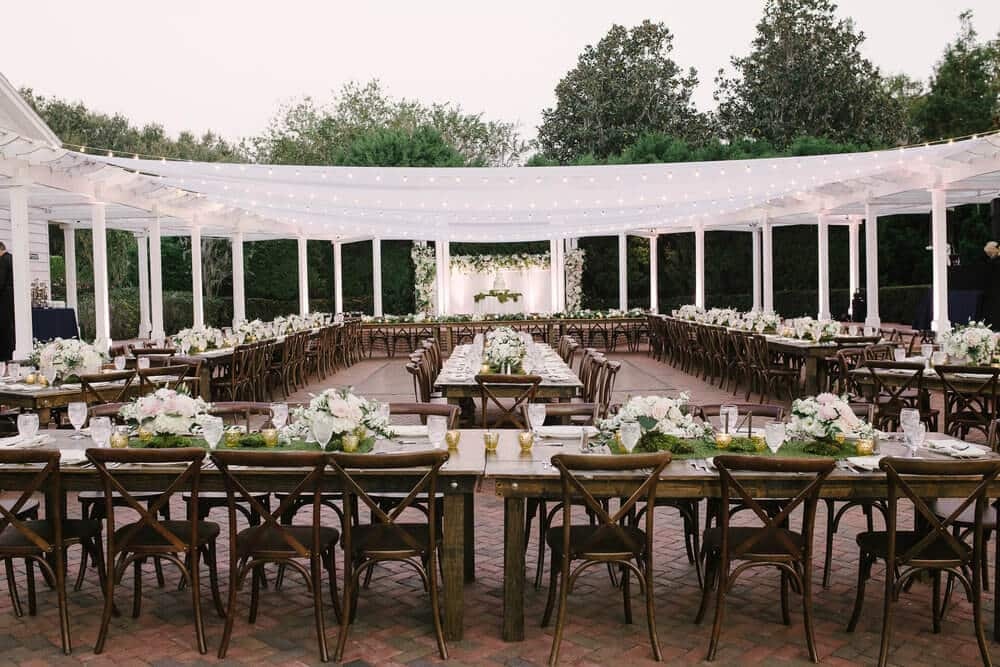 cypress grove wedding reception area with white linen cover and floral table decorations