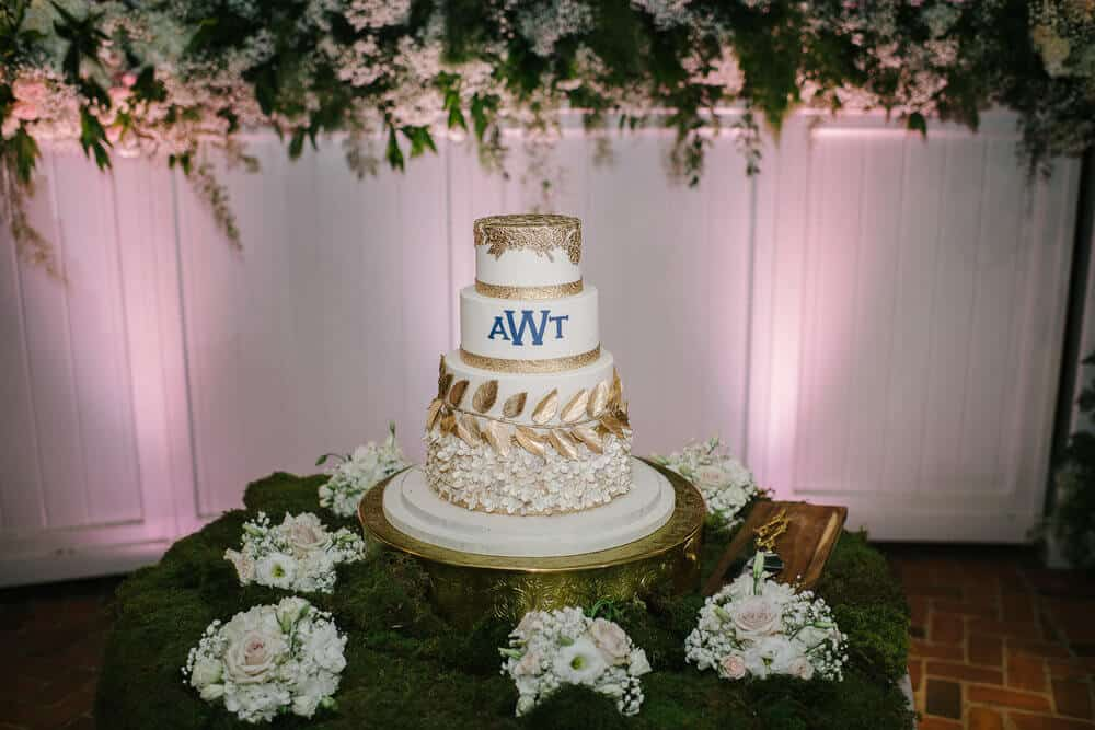 cypress grove wedding cake with gold metallic leaf design on gold cake holder