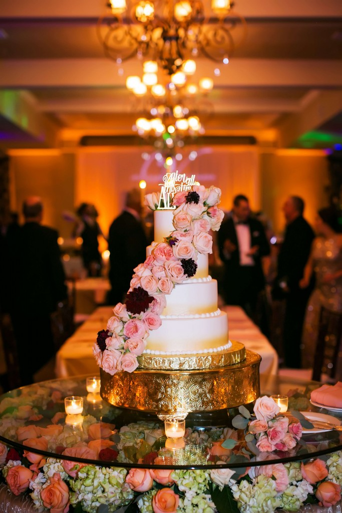 Wedding cake with cake topper. Wedding cake with pink flowers. Amber uplighting.