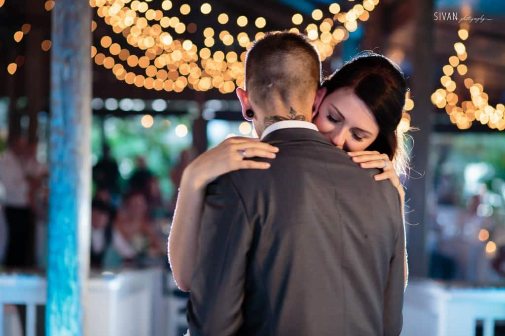 Bride and groom first dance under market lighting