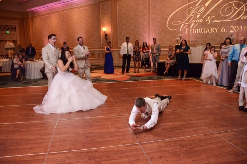 orlando wedding dj - Groom doing the worm for bride on wooden dance floor at Omni Champions Gate wedding - pink uplighting. Tan wedding tuxedos. Layered wedding dress. Wedding gobo.