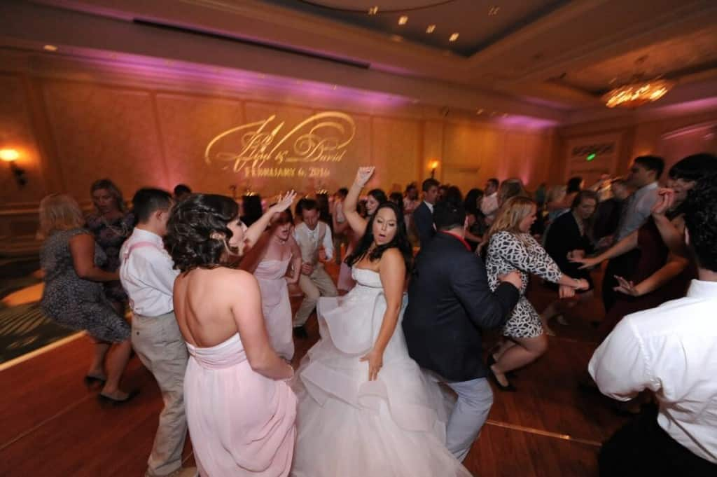 orlando wedding dj at Omni Champions Gate with gobo and pink uplights in background. Layered wedding dress.
