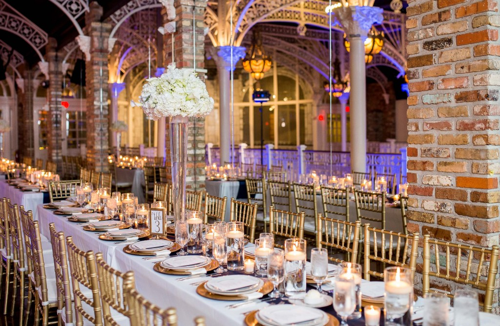 Orchid Garden Wedding reception table  with royal blue uplighting and gold table accents