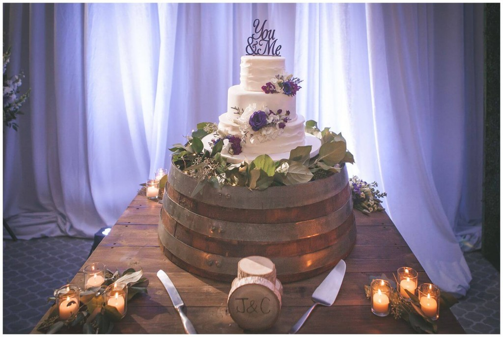 Wedding cake with purple and white flowers on top of wooden cake holder with purple uplighting and white drapes in background