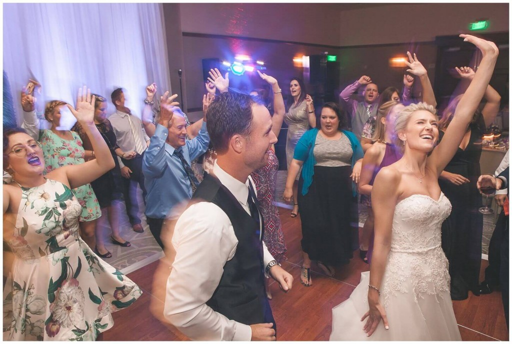 Alfond Inn wedding reception dancing with bride wearing lace fit and flare wedding dress and purple uplighting