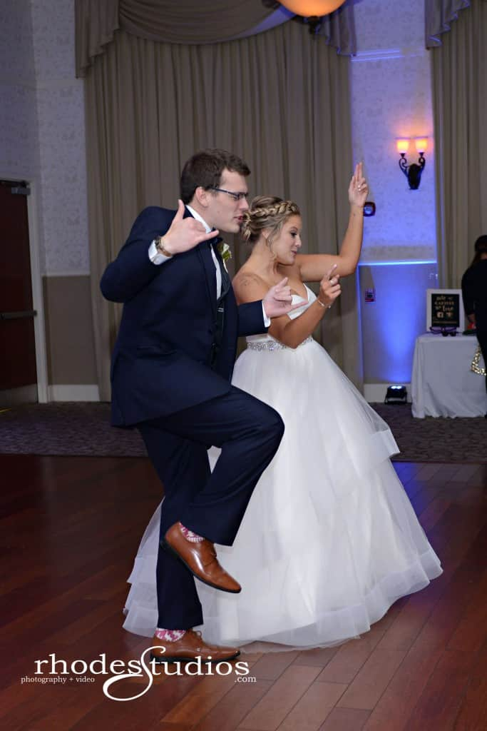 Lake mary events center wedding reception bride and brother dancing on dance floor with royal blue uplighting
