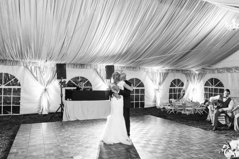 Private residence outdoor tent wedding bride and groom first dance on dancefloor in tent