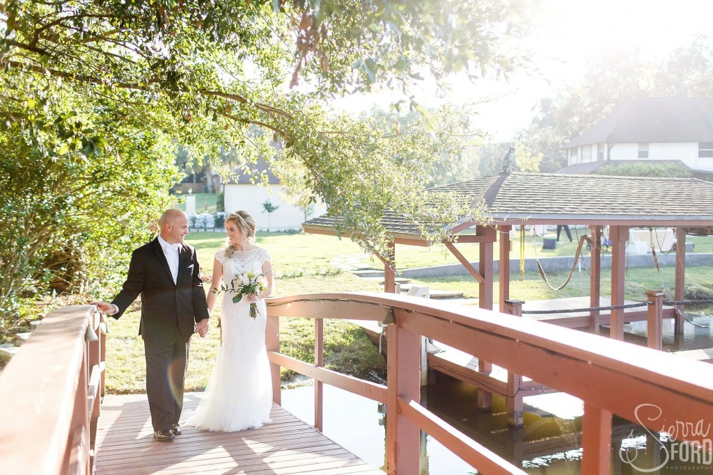 Private residence outdoor tent wedding bride and groom walking on bridge and holding hands outdoors