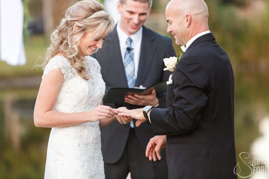 Private residence outdoor tent wedding bride and groom at alter exchanging rings outdoors
