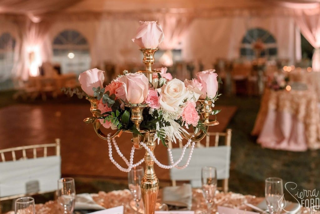 Private residence outdoor tent wedding reception table flower decorations with dance floor in background and light pink and white accents