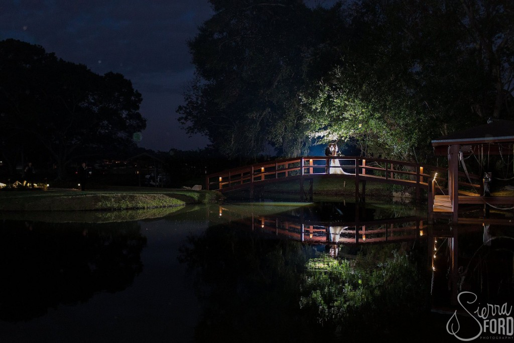 Private residence outdoor tent wedding bride and groom on bridge over water at night outdoors