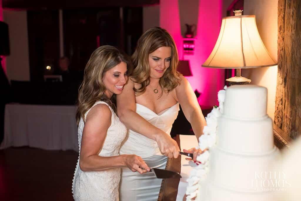 Casa Feliz same sex wedding cake cutting with magenta uplighting