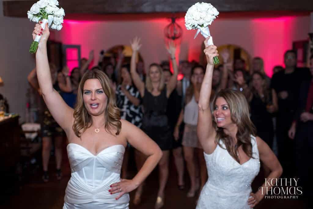 Casa feliz same sex wedding brides doing bouquet toss with magenta uplighting