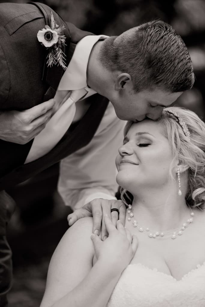 Delamater House bride and groom wedding photo with groom kissing bride on forehead