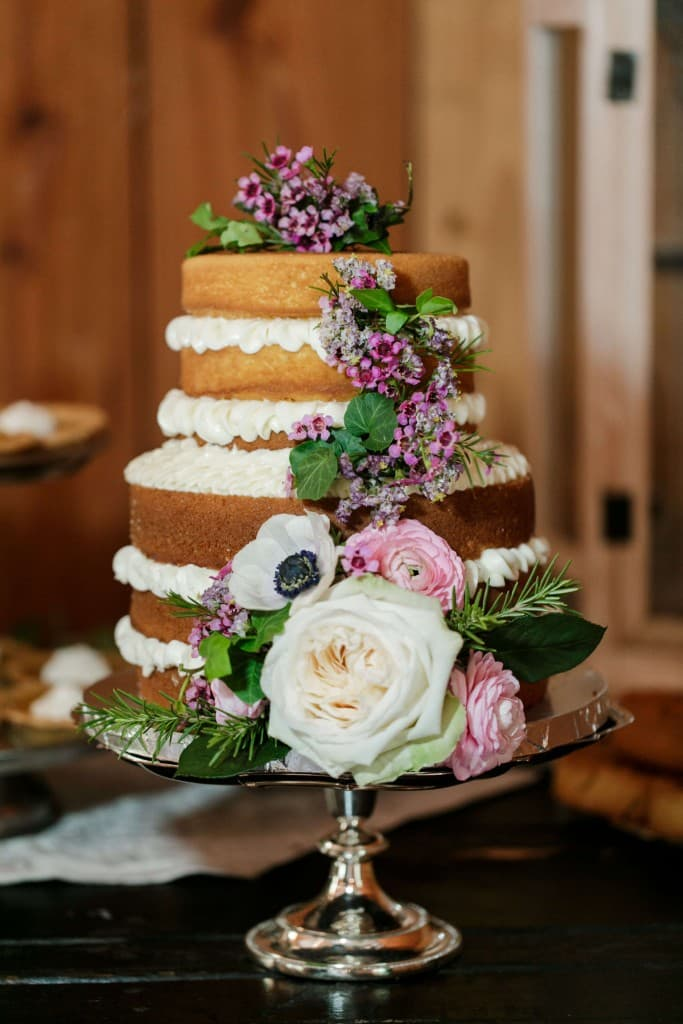 Delamater House wedding cake with frosting on the inside and purple pink and white flowers on the outside