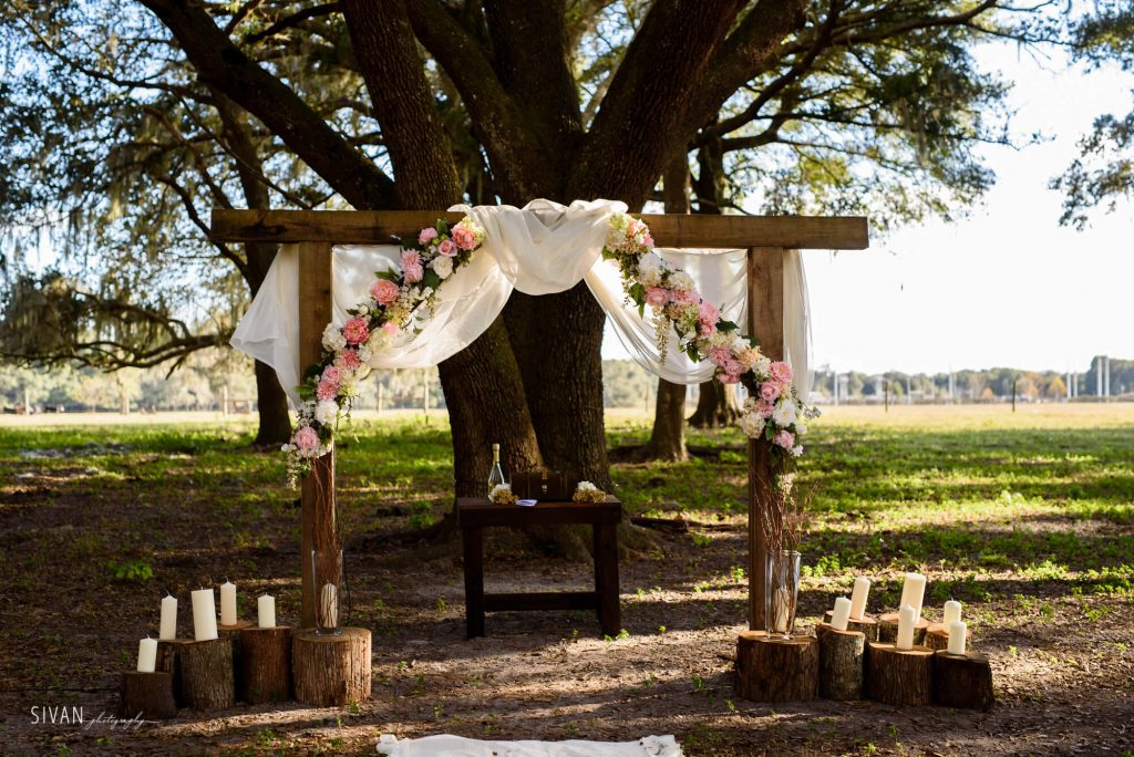 3M Ranch wedding ceremony wooden arch with flowers and candles