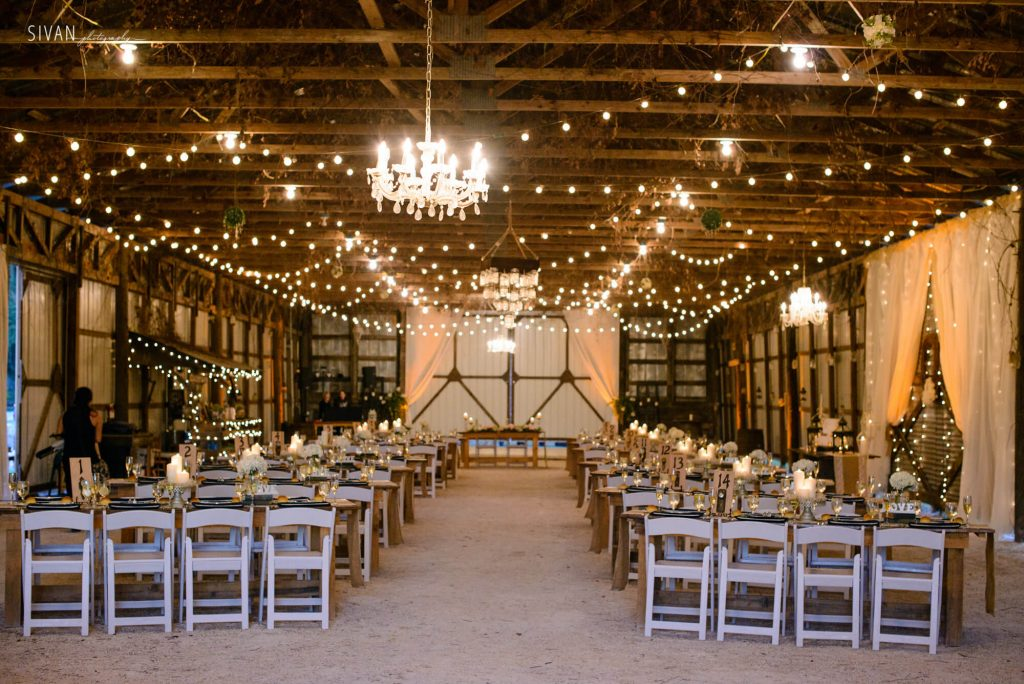 3M Ranch wedding reception area with table settings and market lighting in barn