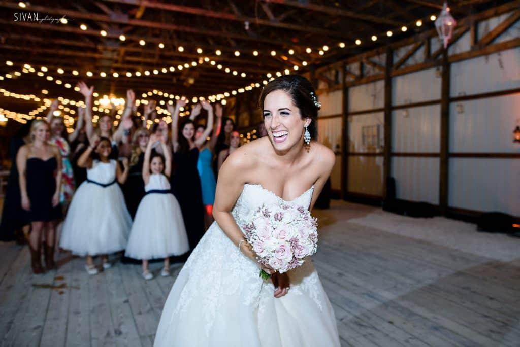 3M Ranch wedding bride tossing bouquet in reception area