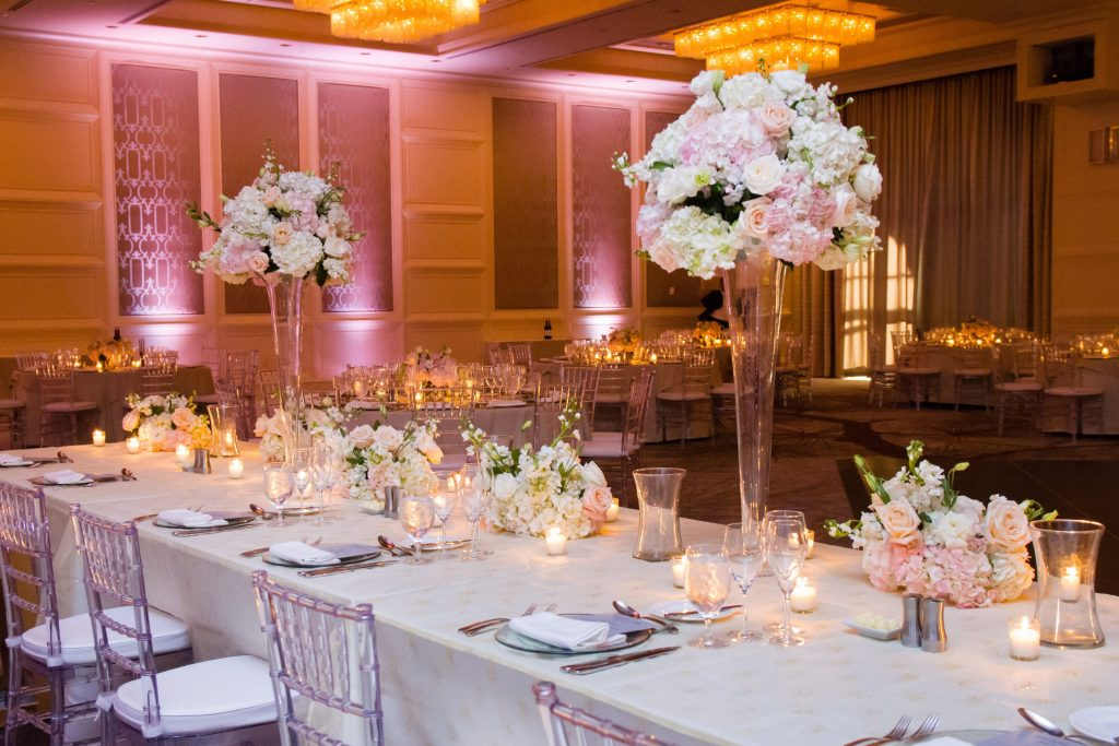 Four Seasons wedding reception set up with light pink uplights