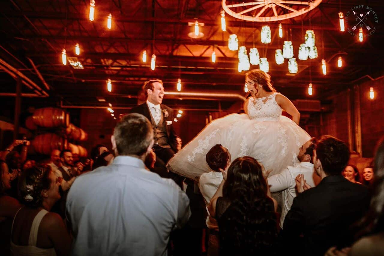 Orlando wedding at Quantum Leap Winery reception bride and groom being picked up in chairs by guest with market lights above