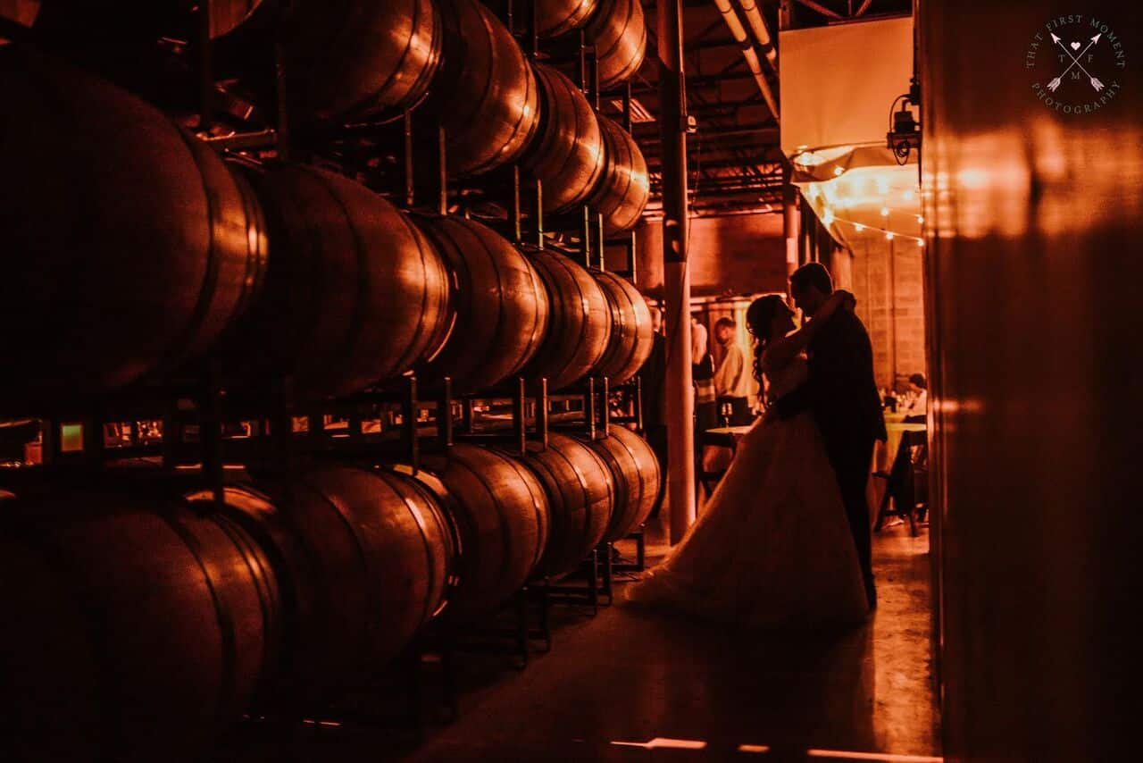 Orlando wedding at Quantum Leap Winery bride and groom pictures by the wine barrels with amber uplighting