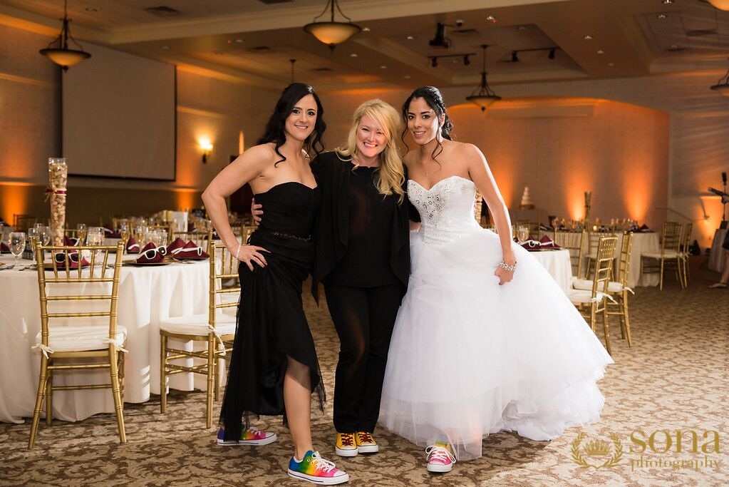Orlando united wedding at Lake Mary Events Center reception area with brides and Our DJ Rocks and amber uplighting