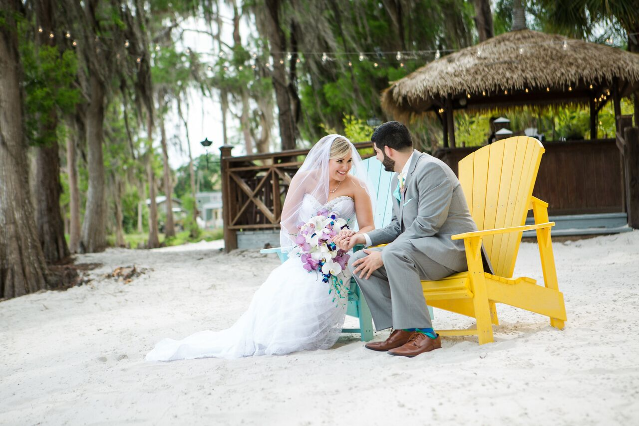 Our DJ Rocks at Paradise Cove beach themed wedding with teal uplighting bride and groom sitting on beach chairs